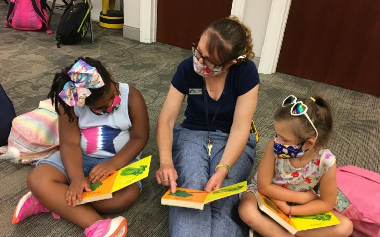 Children reading with library staff member